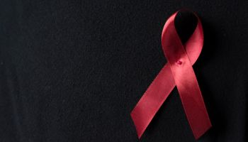 Close Up Of Aids Awareness Ribbon On Black Background