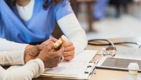 Unrecognizable senior woman asks nurse question about medication