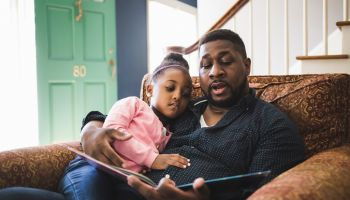 Father and daughter reading book in living room at home