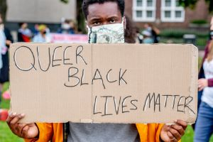 A protester holds a placard that says Queer Black Lives...