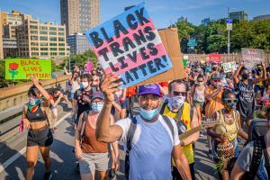 A Black Trans Lives Matter sign held by a participant at the...