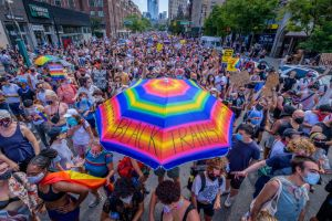 A participant holding a rainbow umbrella over the crowd of...
