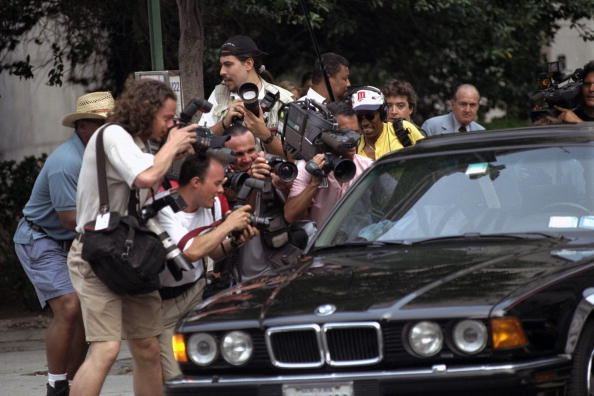 Photographers and TV crews close in on Bill Cosby's car as h