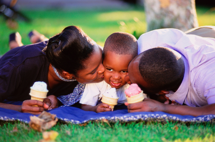 Family lying on grass with ice-creams, parents kissing boy's face