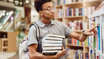 Serious Afro-American high school student in eyeglasses wearing satchel on one shoulder standing in modern library and finding books to prepare for exam