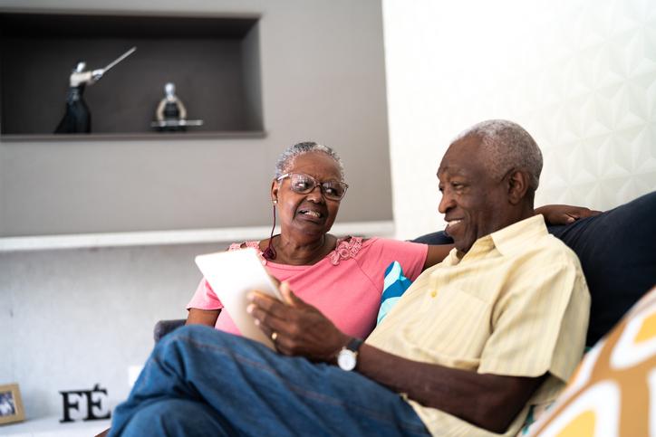 Senior couple using digital tablet at home