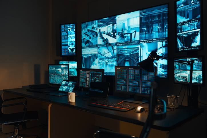 A security workplace with a modern high-tech control panel in the form of large monitors that display real-time information from external video surveillance cameras for 24 hours.