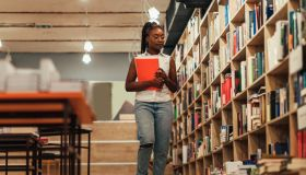 Female student searching for books in the campus library