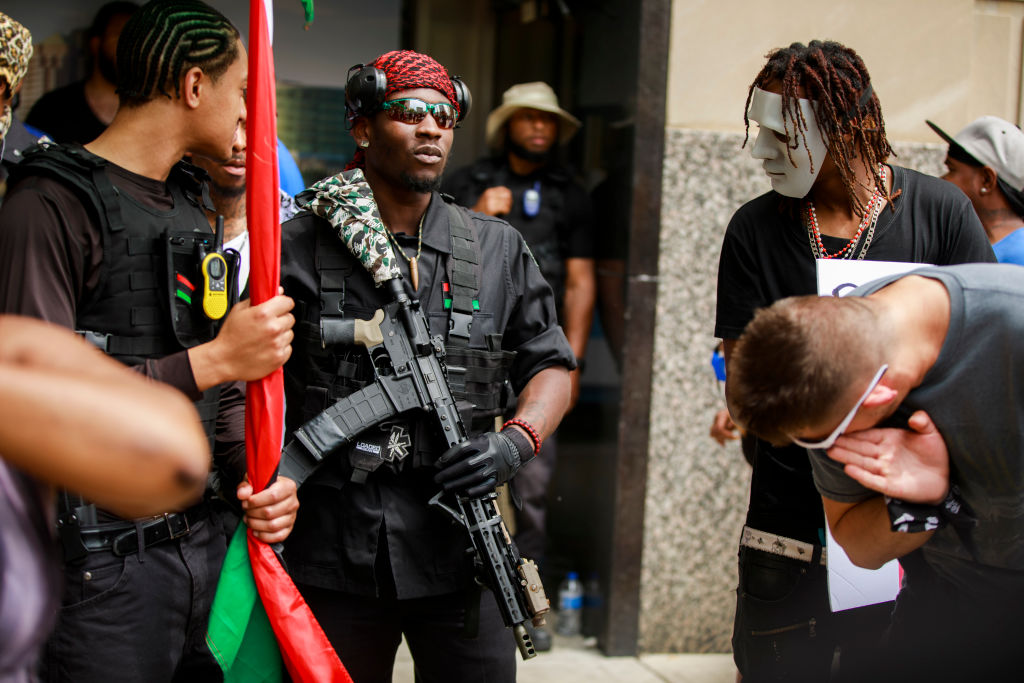 Armed members of the New Black Panthers protest against the...