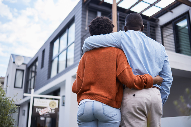 Rearview shot of a young couple standing outside their new home