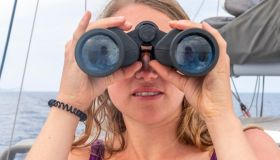 Young woman looking through binoculars, on sailboat, Dodecanese, Greece