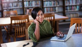 Young African-American woman using laptop in library