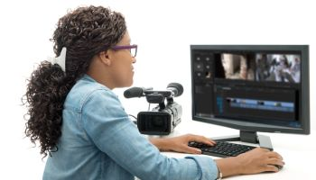 Woman Using Computer By Movie Camera Against White Background