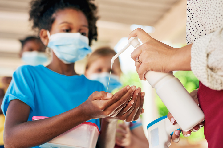 Shot of a young girl wearing a face mask and sanitising her hands during recess at school