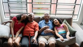 Grandparents and granddaughters laughing at home