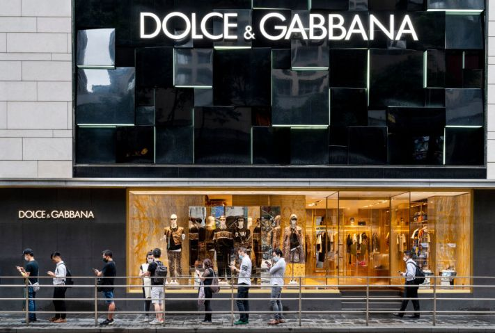 Shoppers stand in front of the Italian luxury fashion house...