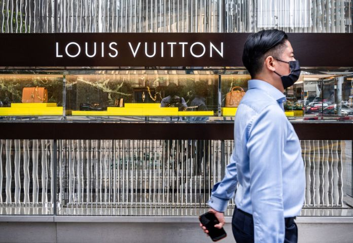 A man walks past the French luxury fashion brand Louis...