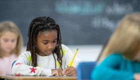 Multi-Ethnic Elementary Students Writing in Class