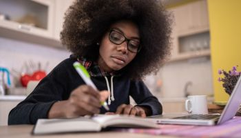 Young african american girl with glasses working and studying at home on a laptop. Covid-19 isolation, home activities