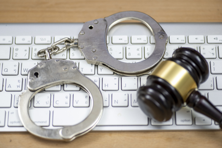 Laptop, wooden gavel and handcuffs on light table, closeup. Cyber crime