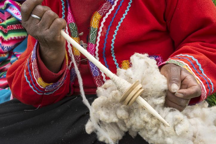 Quechua woman with alpaca wool and tool to spin it into yarn; El Parador de Moray, Sacred Valley, Peru.