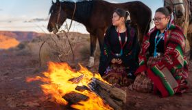 Two Native American Sisters, One Playing A Drum, Wrapped In Traditional Navajo Blankets Staying Warm By The Campfire Horses Behind Them, Iconic Monuments, Sunset