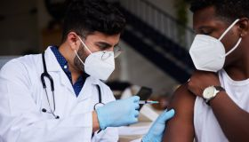Doctor wearing a mask giving a male patient a vaccination in a clinic